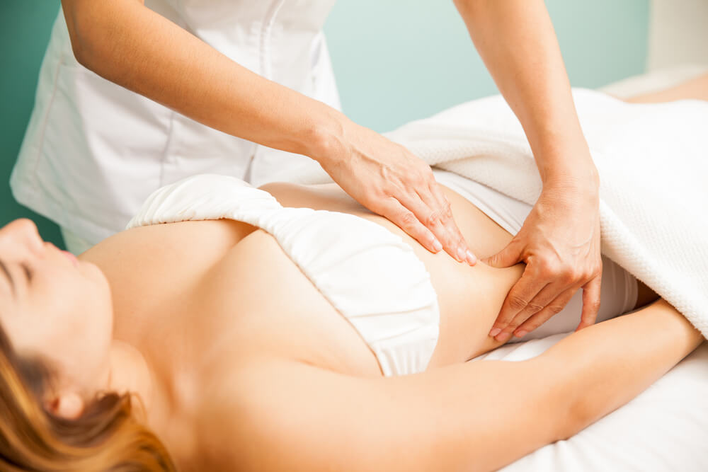 Beautiful young woman getting a lymphatic massage at spa