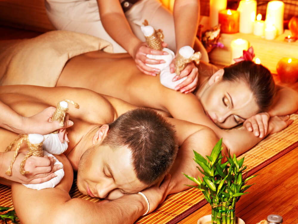Man and woman getting herbal ball massage