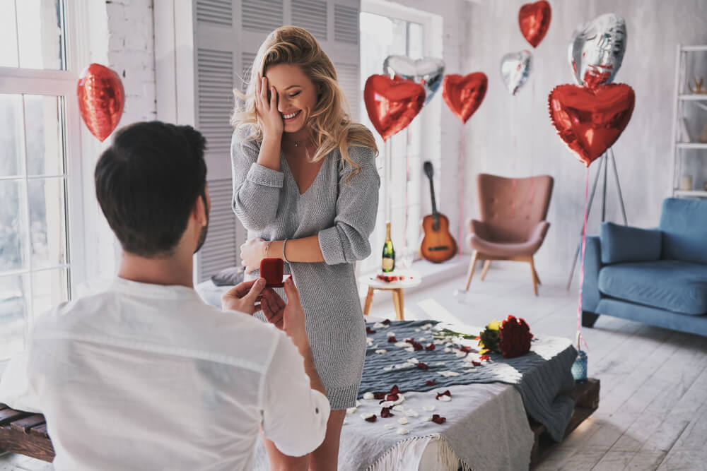 Surprised young woman covering face with hand and smiling while her boyfriend proposing her